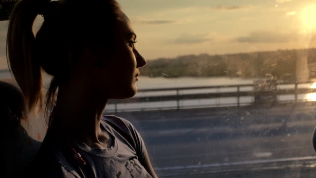 Woman travels in a bus looking out the window at sunset video