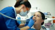 Woman treats teeth at the dentist video