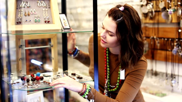 woman trying fashionable necklace in the shop video