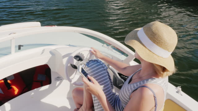 Woman turit hat floating on a boat, using a mobile phone. View from above. Concept: sea holiday in Spain, Europe video