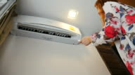 Woman turn on air conditioner video