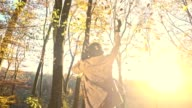 SLO MO Woman twirling under falling autumn leaves video