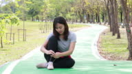 woman tying shoelace in running shoe during jogging video