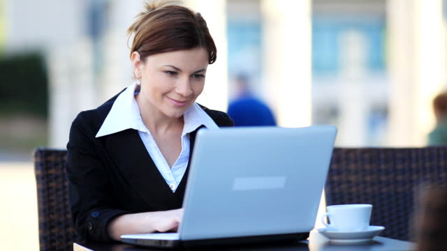 Woman typing at laptop computer and drinking coffee. video