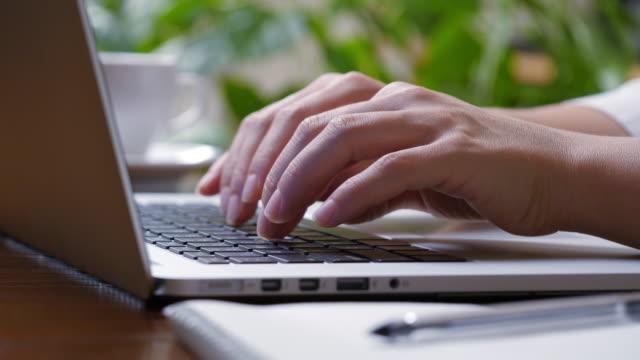 Woman typing on a laptop keyboard. Sliding shot video