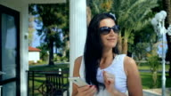 Woman typing on the smartphone in tropical garden. Vacation video