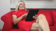 Woman typing with digital tablet on red sofà video
