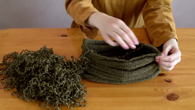 Woman unravelling the knitted hat video