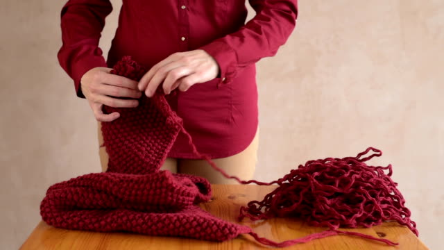 Woman unravelling the red scarf video