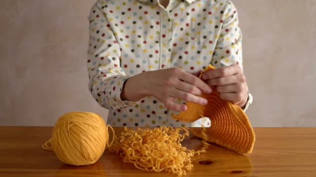 Woman unravelling the yellow scarf video