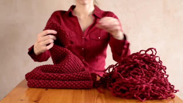 Woman unravels the red scarf. Soft focus video