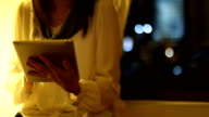 Woman use of tablet pc at night video