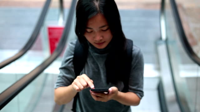 Woman use smart phone in city escalator video