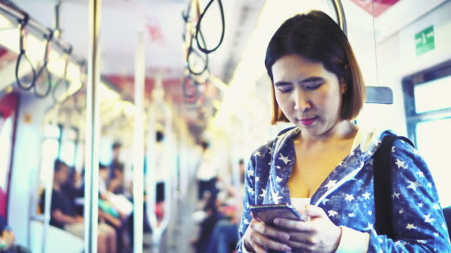 woman use smart phone in sky train. video