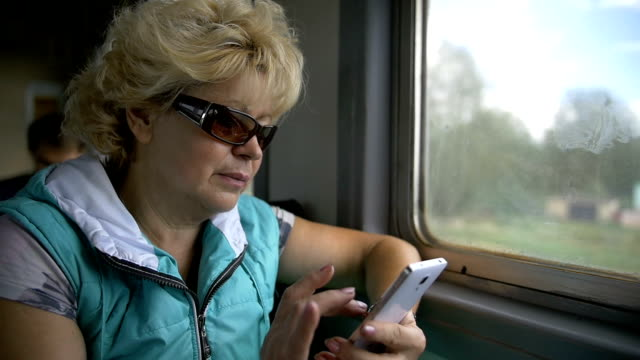 woman use smartphone interior of train, slow motion video