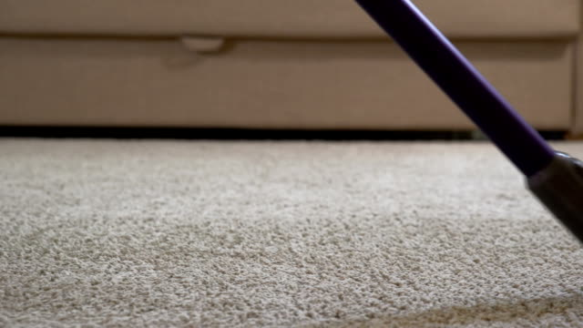 A woman uses a vacuum cleaner to clean the carpet. Close up video