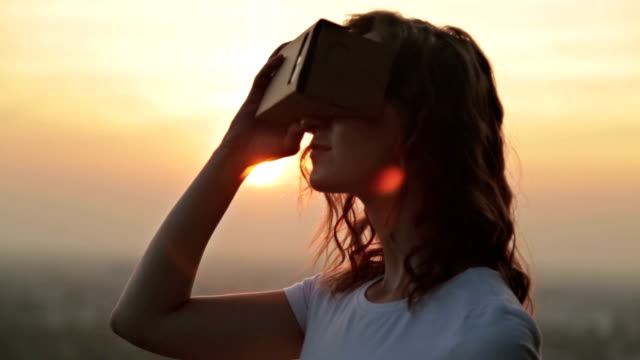 Woman uses a virtual reality glasses at sunset video