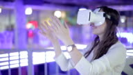 A woman uses a virtual reality glasses in entertainment center. video