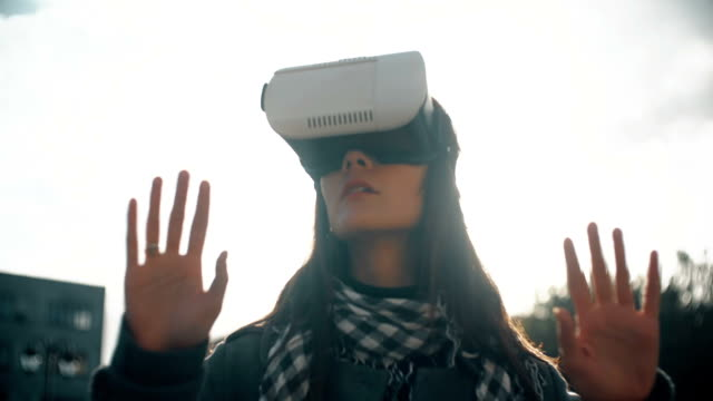 woman uses a virtual reality glasses in rear light at sunset FullHD video