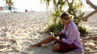 Woman uses digital tablet on beach, below leafy tree video