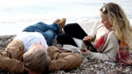Woman uses digital tablet on deserted beach video
