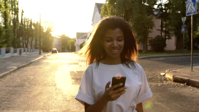 Woman uses smartphone in city at sunset video