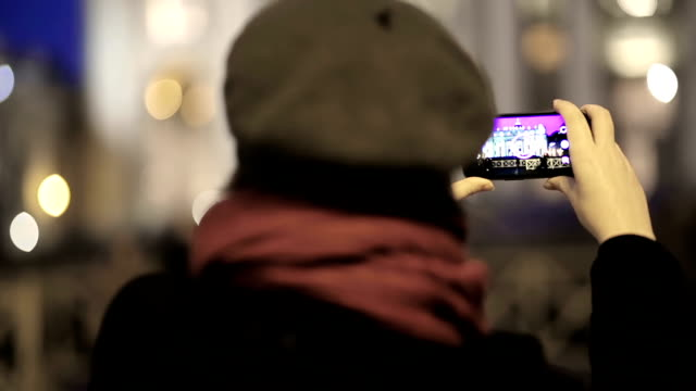 Woman uses smartphone to take a photo at night video