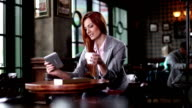 Woman using a digital tablet at a coffee shop video