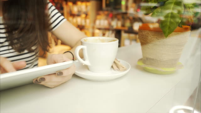 Woman using a digital tablet in coffee shop. video