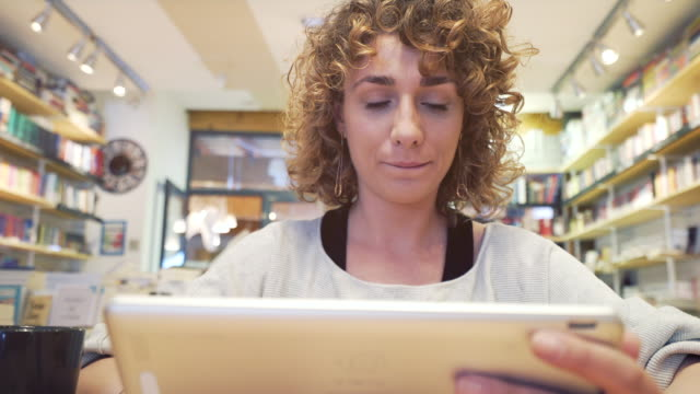 Woman using a digital tablet in the library. video