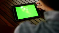 Woman using a digital tablet PC with green screen video