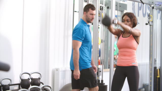 Woman using a kettlebell weight with a trainer in a gym video