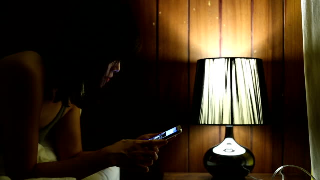 Woman using a smart phone on bed video