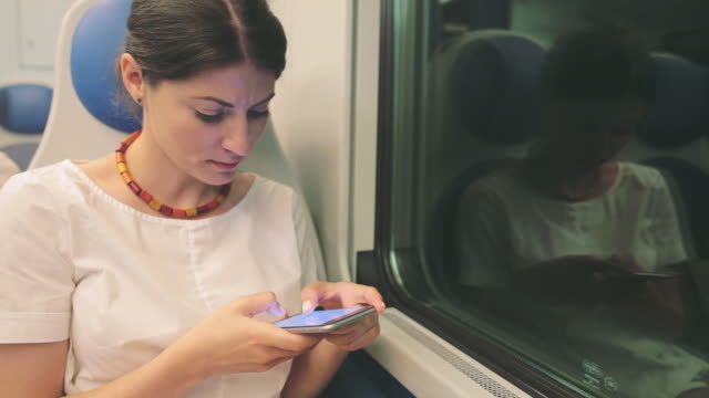 Woman using a smart phone while traveling by train. video