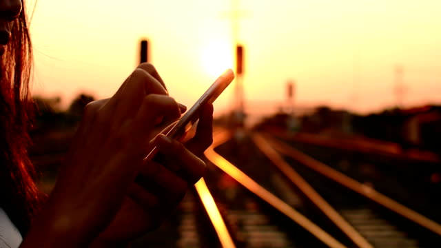 woman using a smartphone on the railway. video