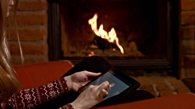 DS Woman using a tablet computer by the fireplace video