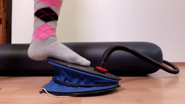 Woman using air pump at the air mattress video