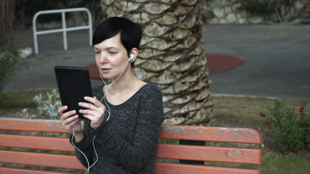 Woman using app on touch screen tablet for video call at playground video