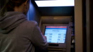 Woman using ATM outdoor in the evening video