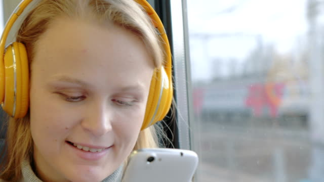 Woman using cell and listening to music in the train video