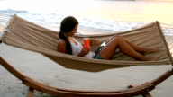 Woman using digital tablet and having mocktail on a hammock video