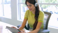 Woman Using Digital Tablet And Headphones In Design Studio video