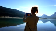Woman using digital tablet by the lake video