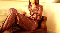 Woman using Digital tablet by the Window in Pyjamas video