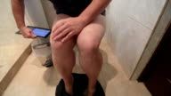 Woman using digital tablet computer while sitting on a toilet in bathroom video