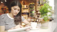 Woman using digital tablet in a coffee shop. video