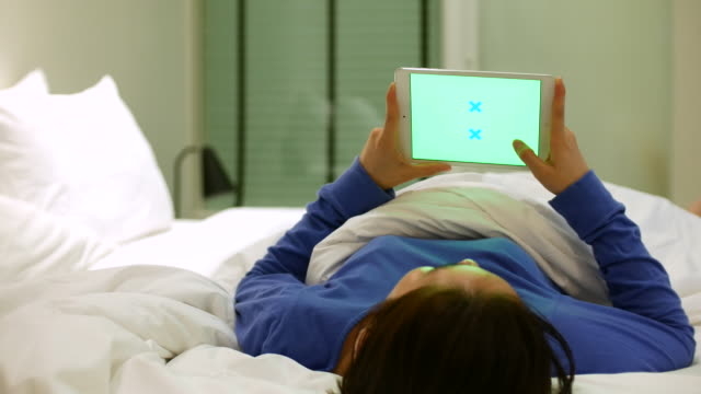 Woman using digital tablet in bed with Green screen, 4k(UHD) video