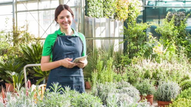 Woman using digital tablet in garden center video