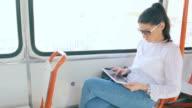 Woman using digital tablet in tram. video