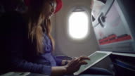 Woman using digital tablet on airplane video